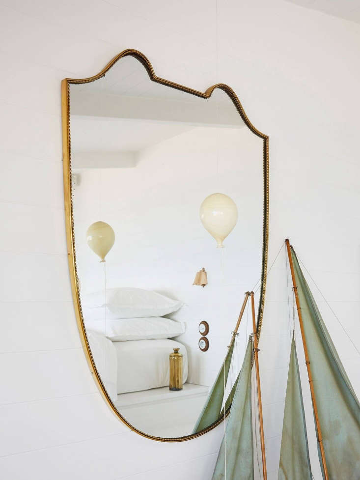 A shield-shaped antique mirror bought in Paris makes the room feel bigger.