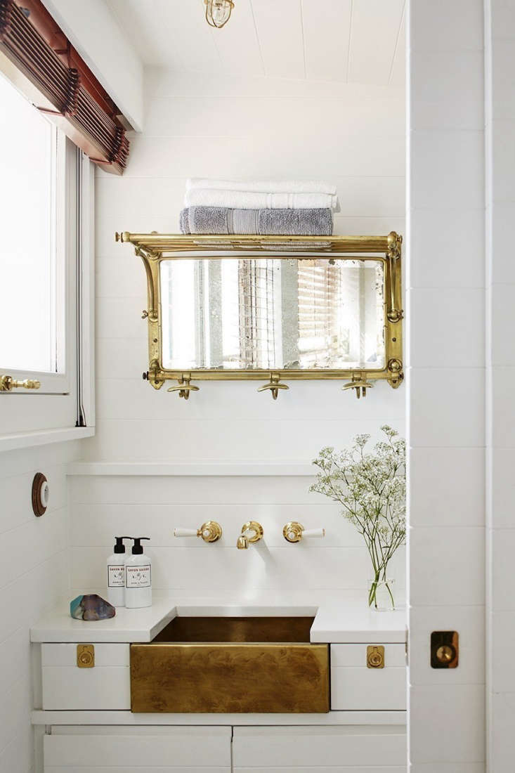 the compact bathroom has a custom patinated brass sink and lefroy & brooke  18