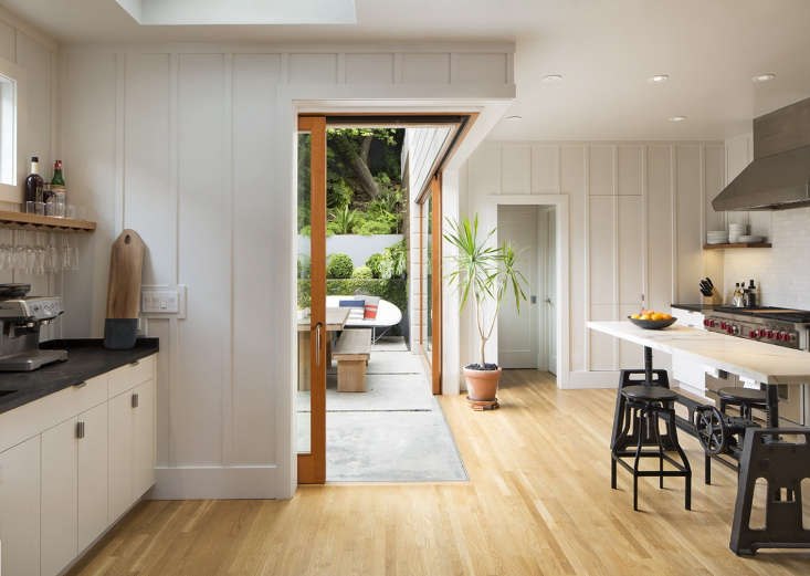 By excavating an inaccessible sloping section of the garden, Davis gained space to insert an addition, a separate pantry and powder room at the far end of the room, as well as a dramatic &#8