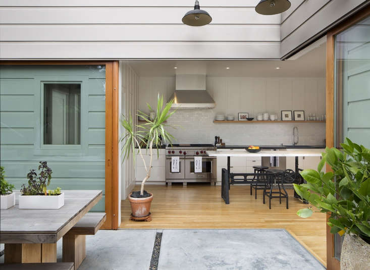 Sliding glass doors, set on a corner and with hidden drains, connect outdoor dining space to kitchen in A Modern Farmhouse Kitchen in SF designed by Malcolm Davis.
