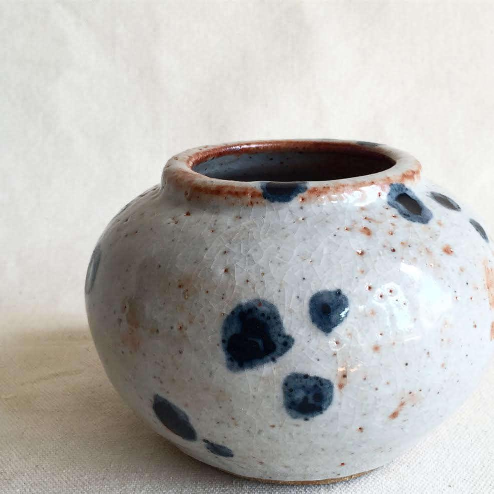 A stoneware vase features indigo dots.