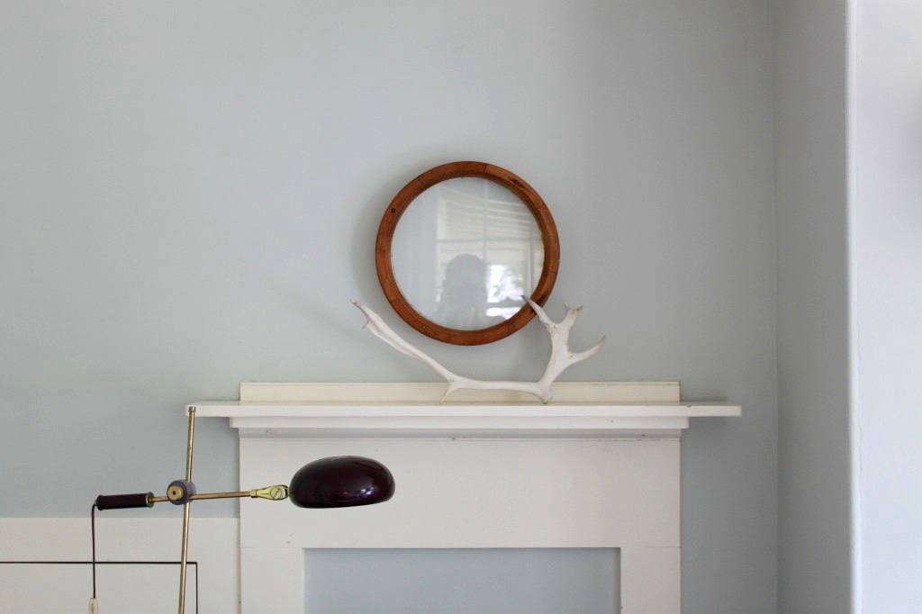 In my own Cape Cod cottage, I created a minimal mantel display by pairinga single vintage porthole with ableached caribou antler thatmy stepfather found in Alaska. See more atThe Soulful Side of Old Cape Cod: Justine's Family Cottage.
