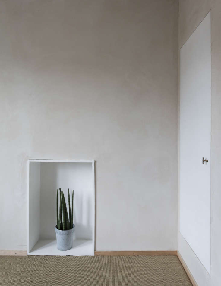 A plant niche and flush closet door are set off by Clayworks&#8