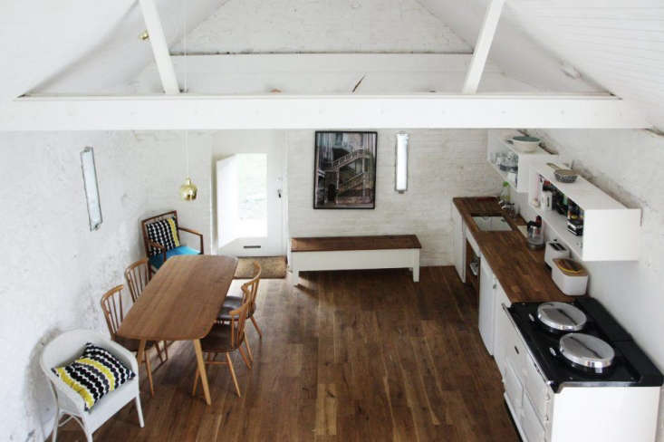 The new oak floor is finished with a Danish oil; it was laid over a new slab concrete base and outfitted with radiant floor heating. The kitchen, complete with Aga, has butcher block counters stained to match the floorboards.