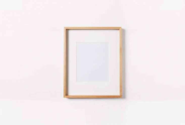 Artwork is framed in a light wood frame. Something similar is the Thin Wood Gallery Framemade of bamboo; $ to $9 at West Elm.