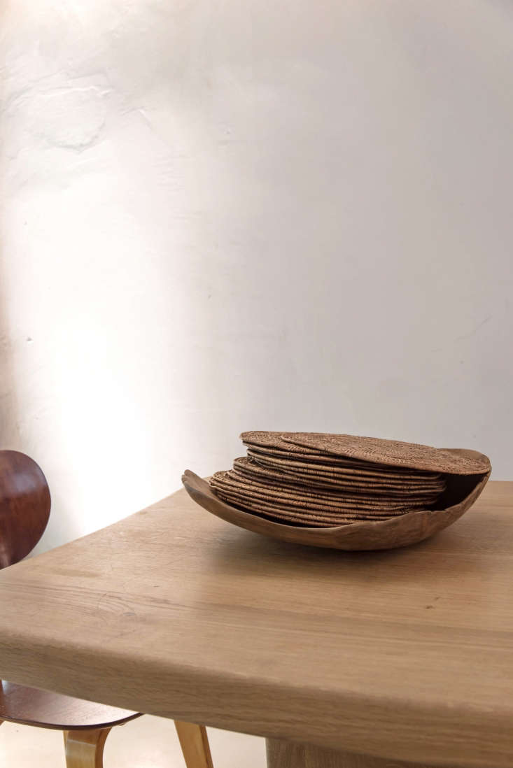 For an impromptu table setting, stack napkins, placemats, and glassware on the table and set out vintage baskets heaping with flatware. Here, woven placemats become a design object when set in a wooden bowl. (De Villeneuve sourced design elements that would feel &#8