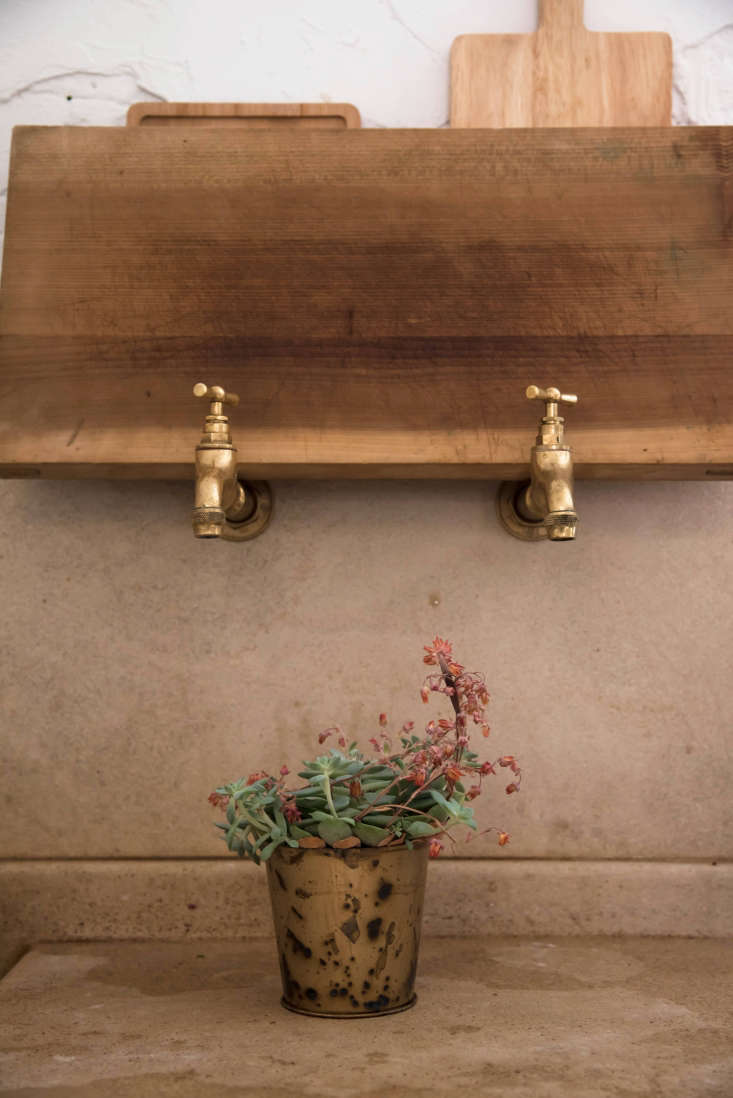 Brass spouts set into the wall water plants, and, as shown here, also serve as impromptu holders for cutting boards.
