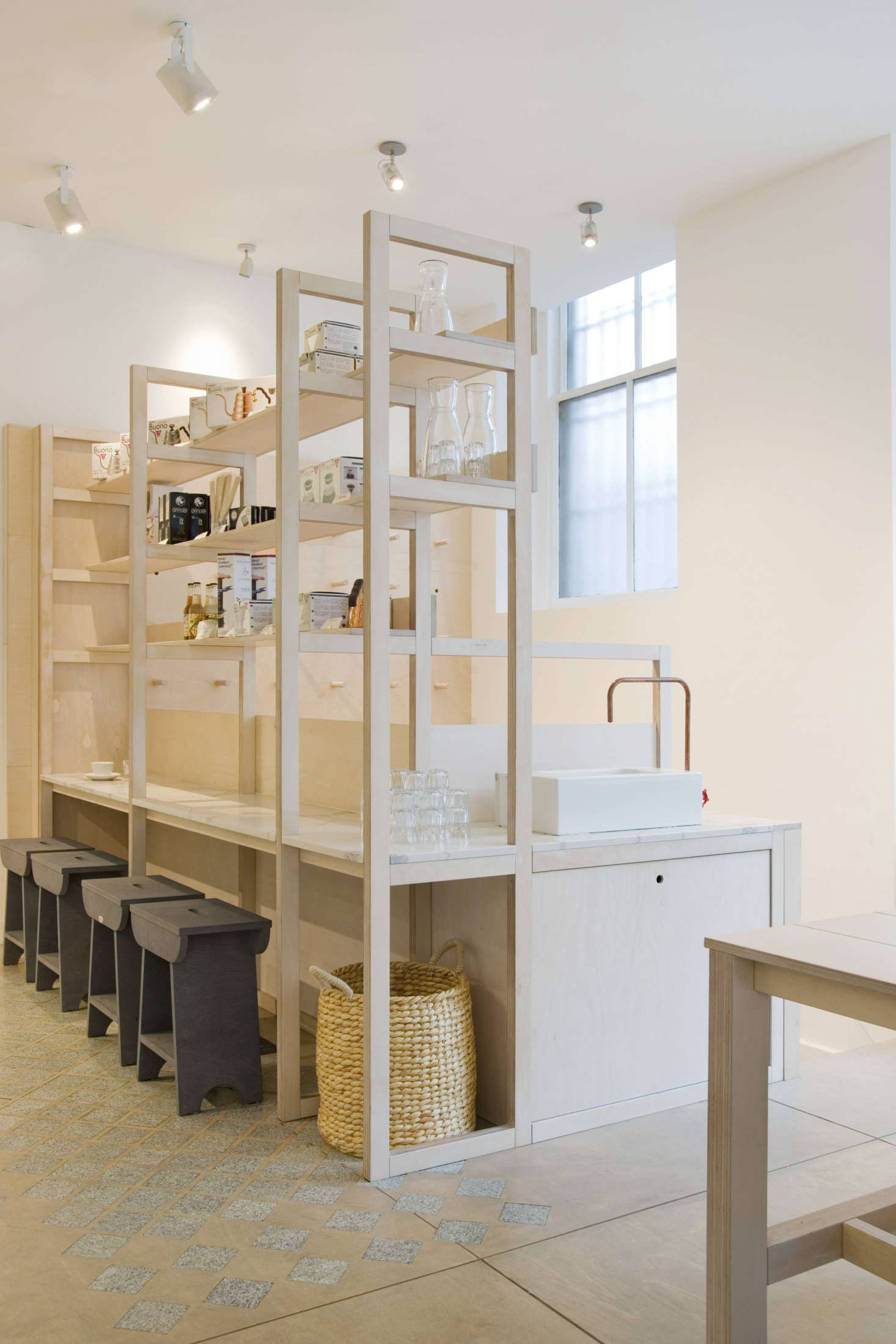 A two-in-one small space idea: When set at the right height, the bottom portion of shelving can serve as a low counter or table, as it does here. Pair with low stools for below-storage seating. (Also shown: the patterned &#8