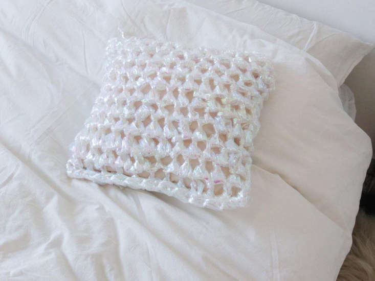 the iridescent aurora pillow is a chunky crochet made from cellophane yarn; \$\ 10