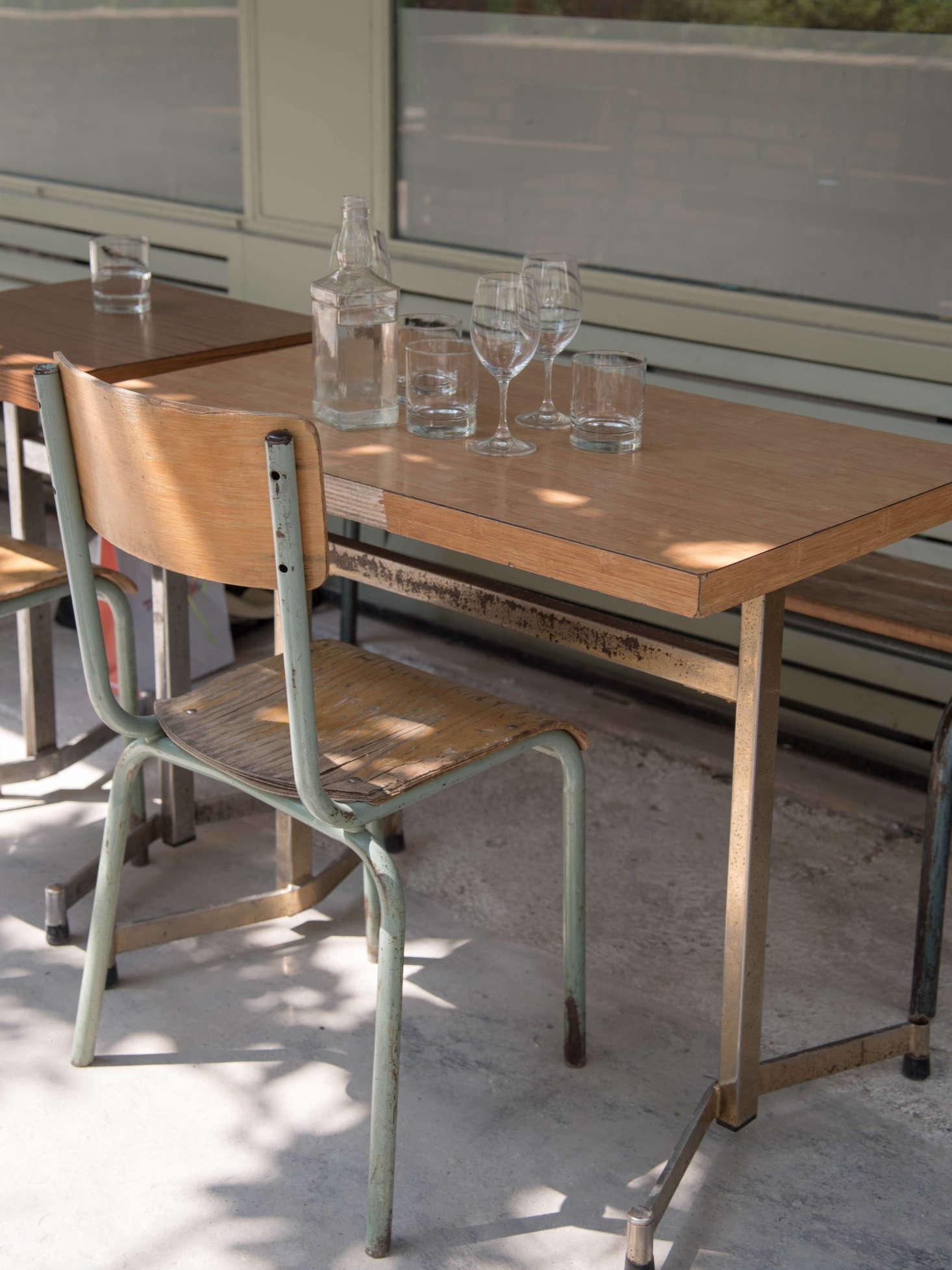 Outsidearevintage French school chairs and tables, sourced from a local brocante dealer. The team collected the glass water carafes(&#8