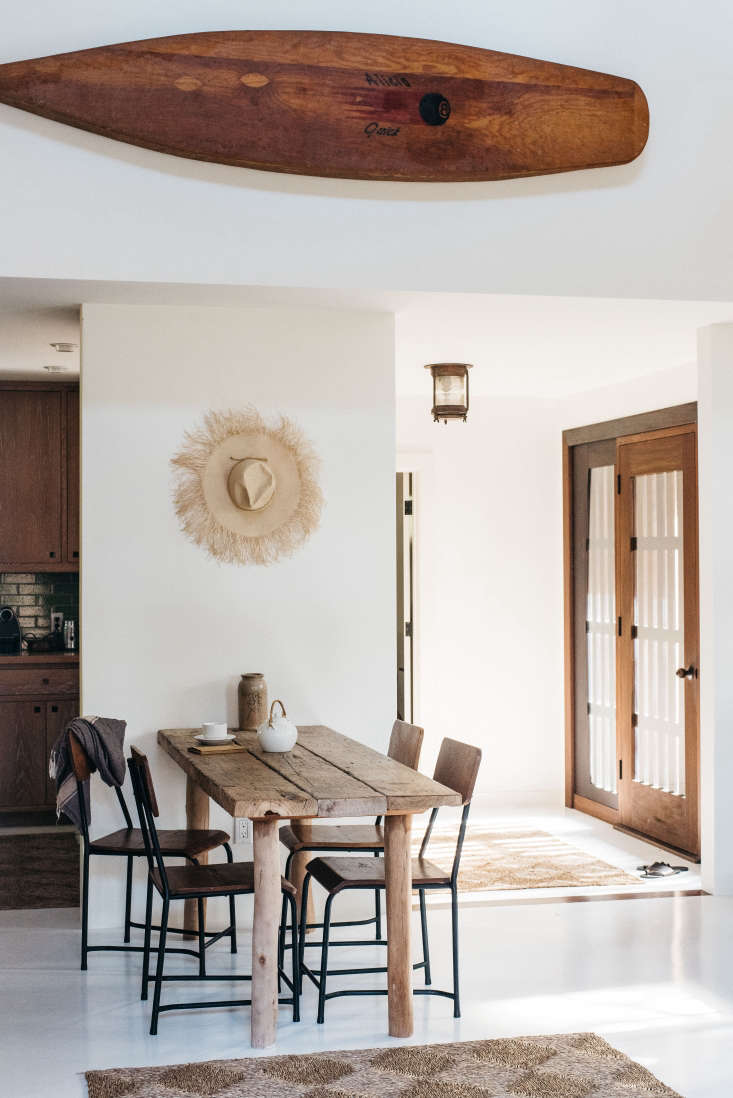 a straw hat serves as decor above the dining table. 16