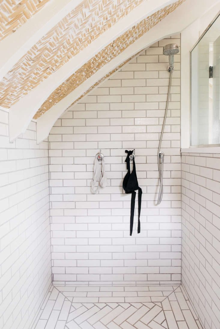 a bathing suit hangs to dry in the shower. the white subway tiles areboneyard 24