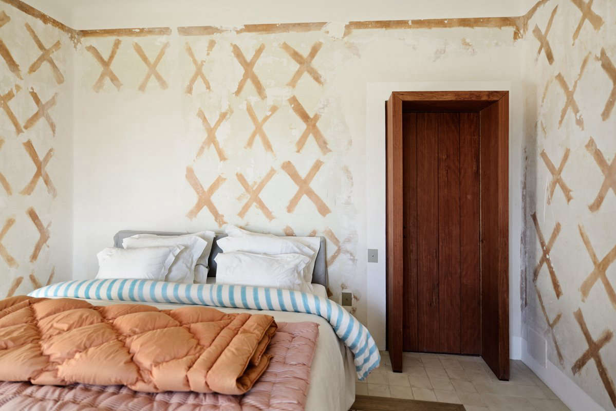 When the old wallpaper was removed, the glue used to apply it left behind the fresco-like X shapes that now pattern this bedroom.
