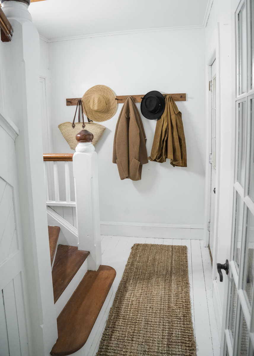 The sparse entryway has a peg rail from Peg & Rail. (SeeObject Lessons: The Shaker Peg Rail.)
