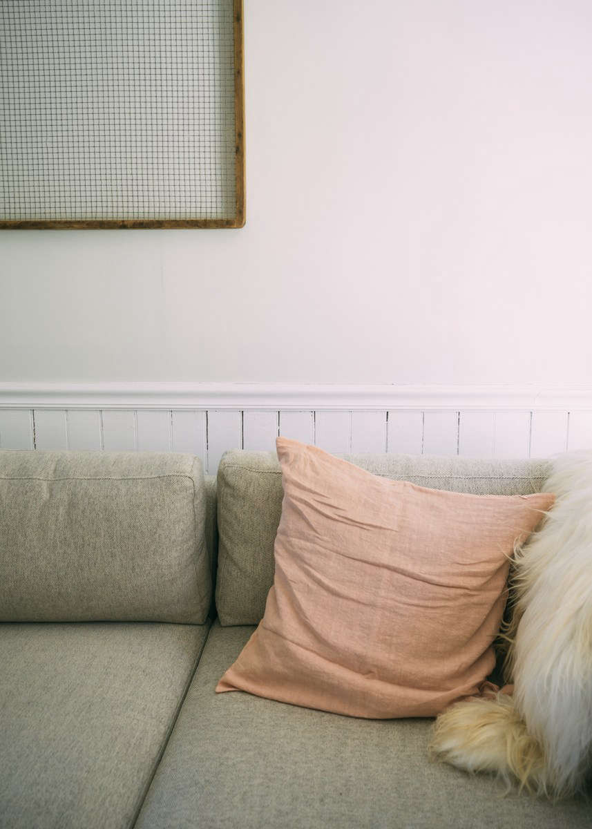 A vintage screen, a gift from a friend, hangs above a West Elm couch. The blush throw pillows are from Hawkins New York.