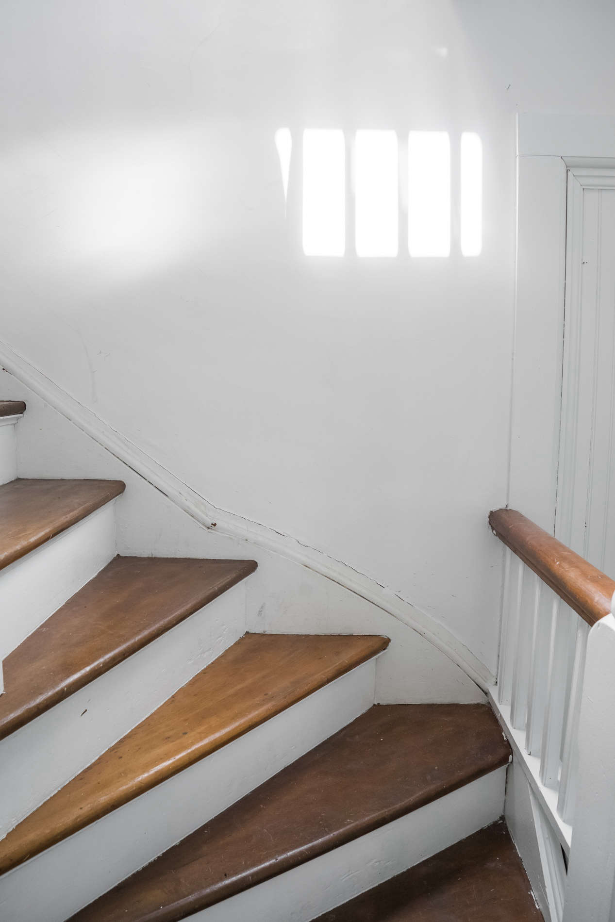 Throughout, original charm and simplicity was left intact. Przystup painted the stairs in Sherwin Williams Extra White and left the original wood treads.