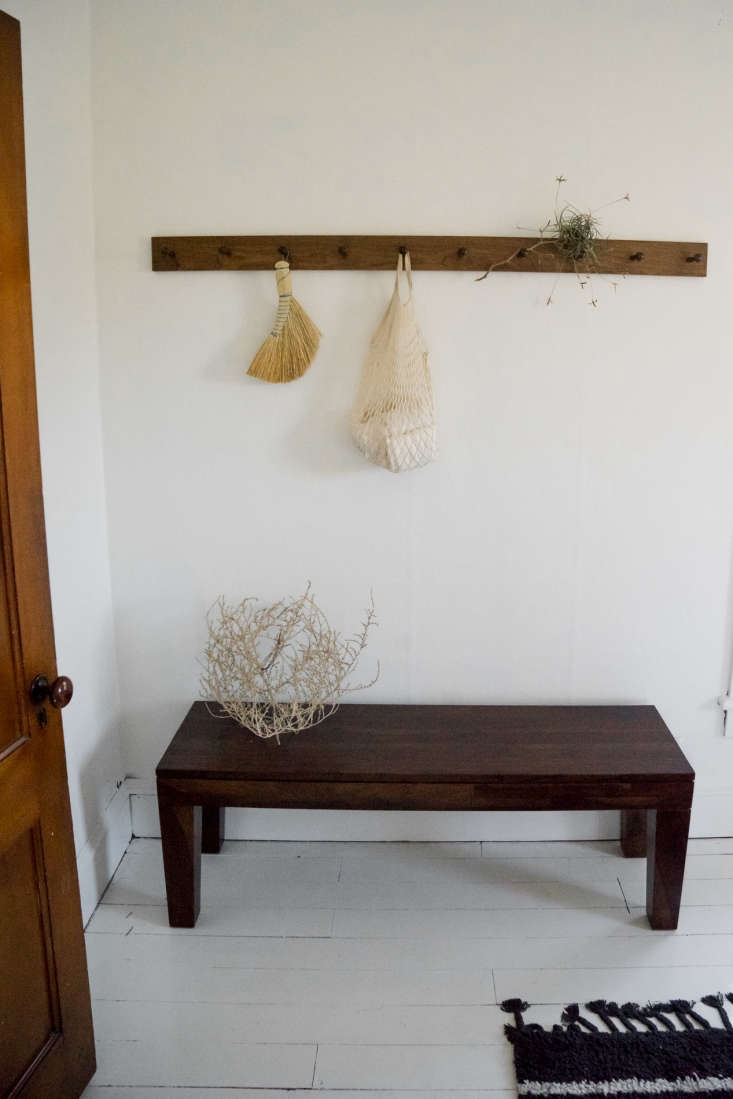 at the foot of the bed, another peg rail holds a redecker hand broom and dried  24