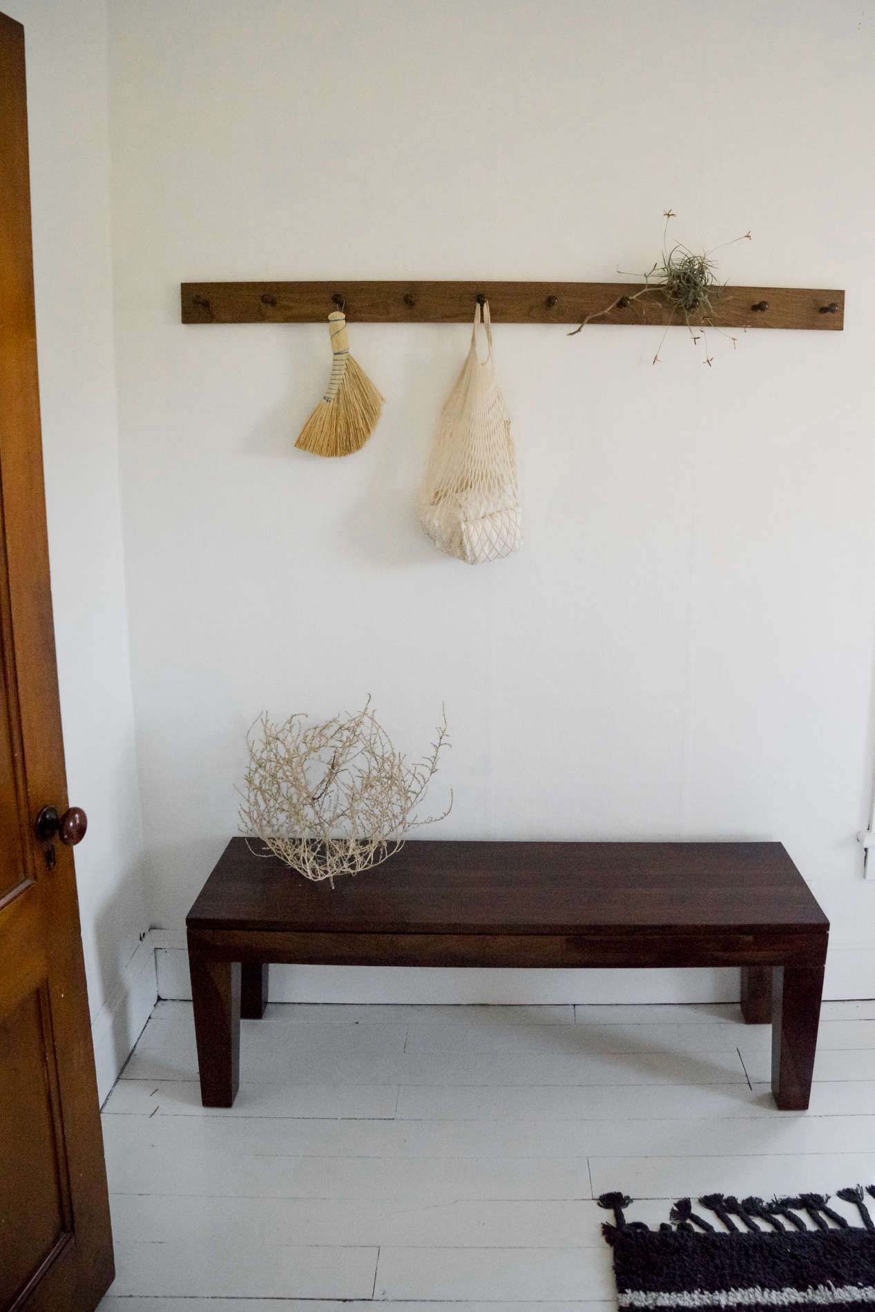 At the foot of the bed, another peg rail holds a Redecker hand broom and dried tumbleweeds.