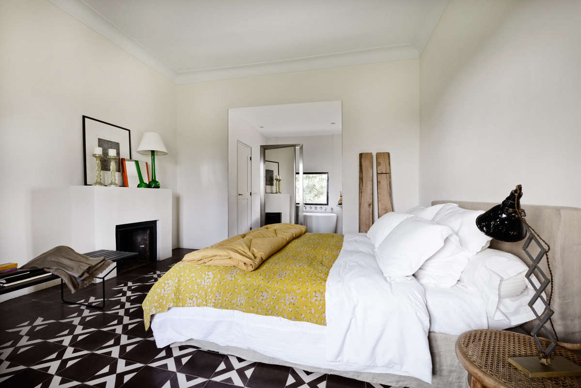 The same Carocim cement tiling in the entry reappears in a bedroom with a sculptural mantel. &#8