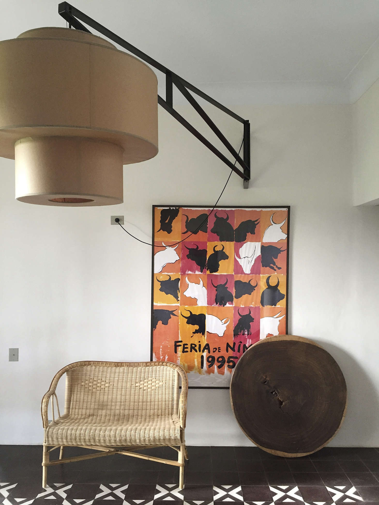 One of the two owners of the house designed the swing light with outsized paper shade; the slice of ebony is a tabletop used as art.