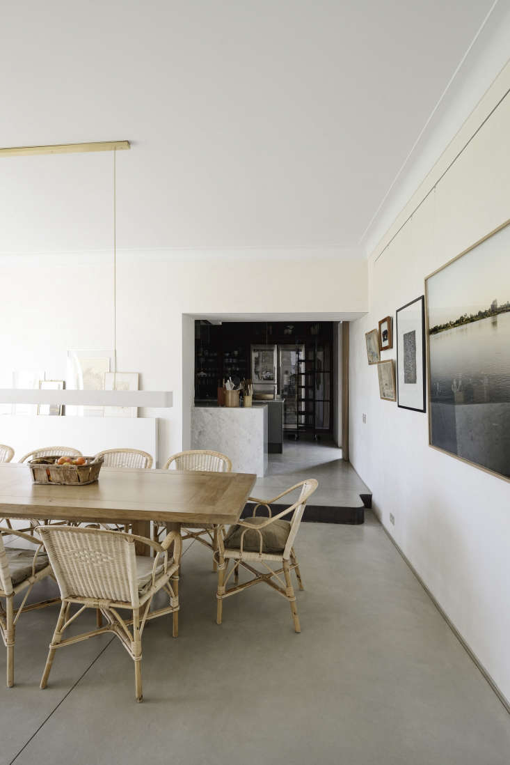 One side of the dining room features artwork propped on a ledge while the other utilizes a thin picture rail for hanging. Photograph by Katrin Vierkant, courtesy of LSL Architects.