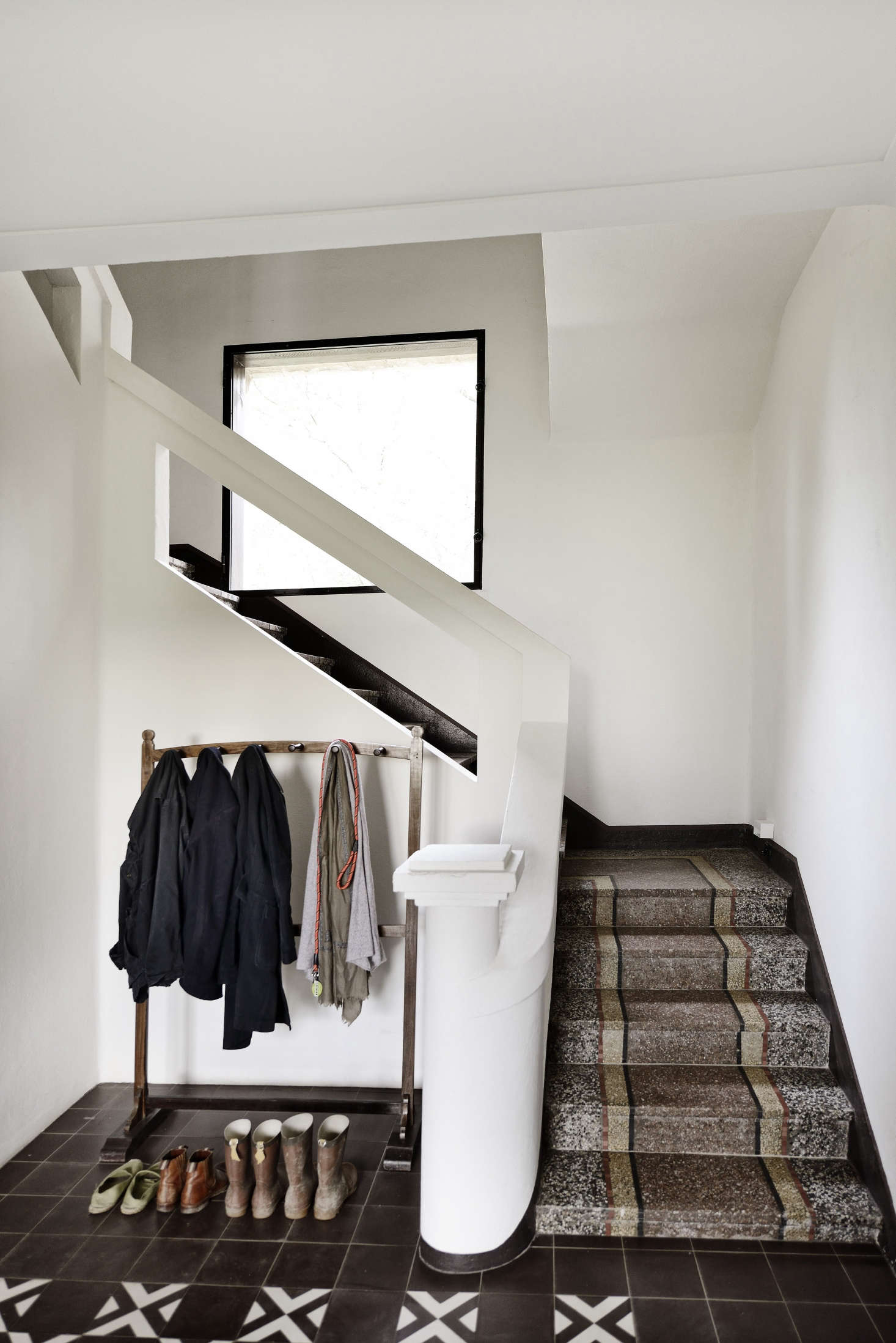 The entry features restored terrazzo stairs and brown-and-white tiles from Carocim of Aix-en-Provence, specialists in classic cement tiles. The oak hanging rack is vintage.