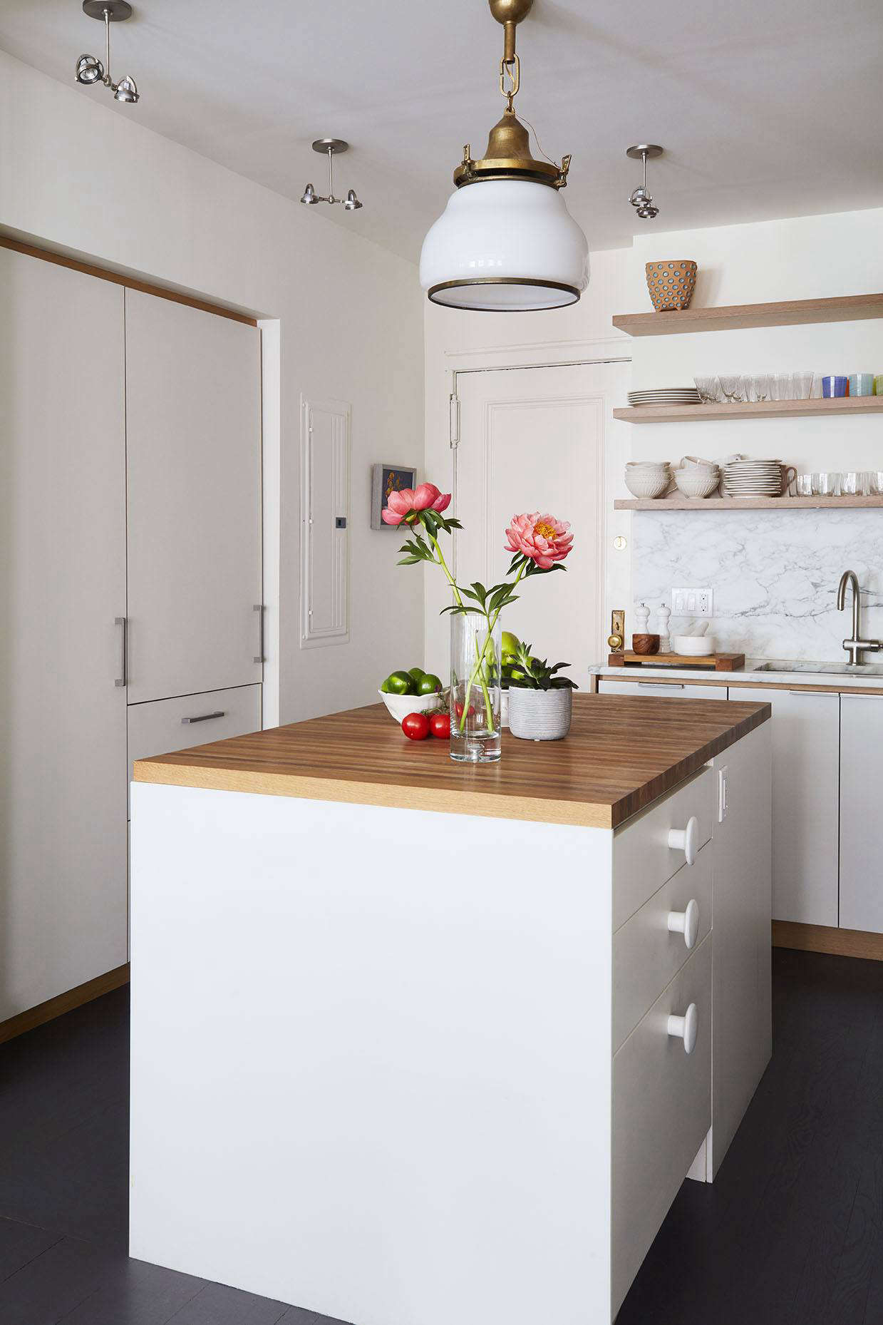 The refrigerator is concealed behindan integrated panel that disappears into built-in storage to the left. On the kitchen island, the designers used oversizeWhite Muuto Dots as drawer pulls. The large glass and brass pendant light is an antique from Dallas sourced by Terbovich.