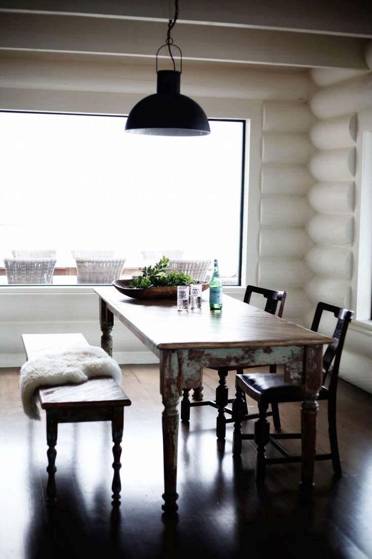 Picked for its patina, the dining table, from Seattle antiques shop Susan Wheeler Home, has the best views in the cabin. The black pendant light, a discontinued design from Wisteria, &#8