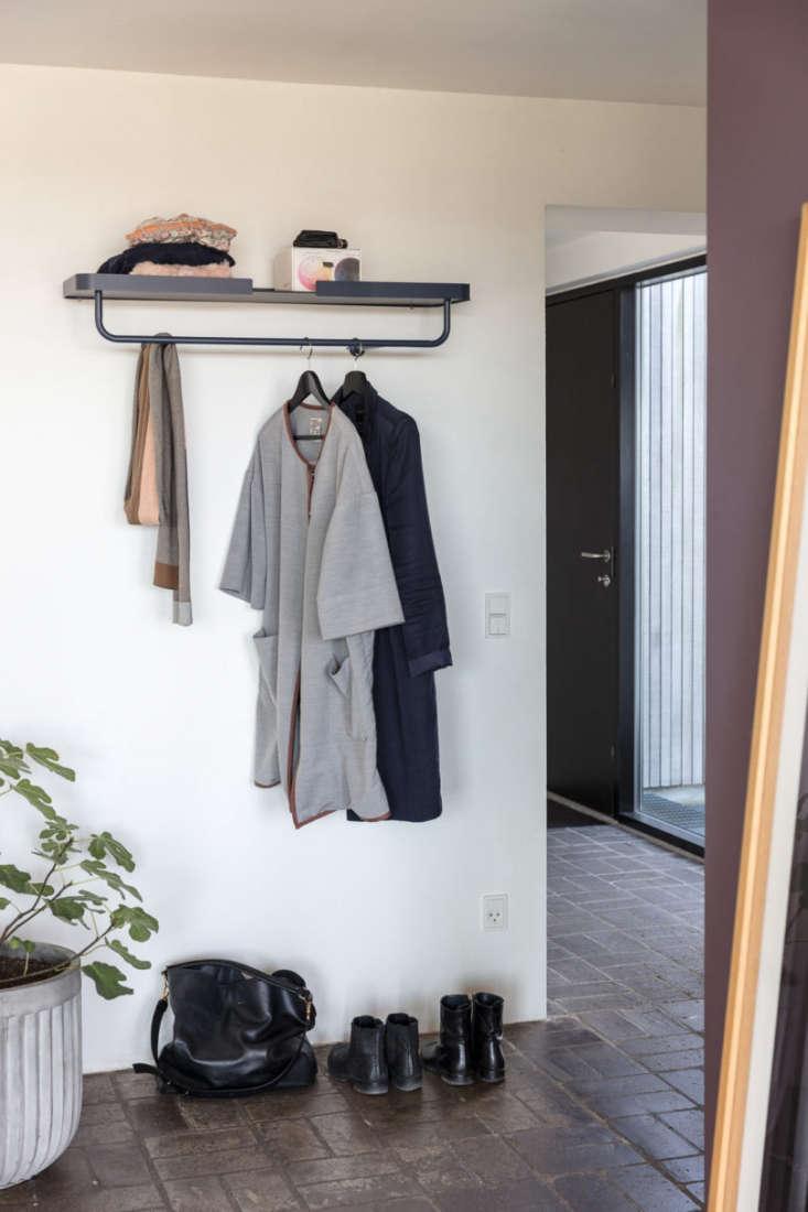 the wall mounted coat hangerin midnight blue (shown) and bone has a metal rai 15