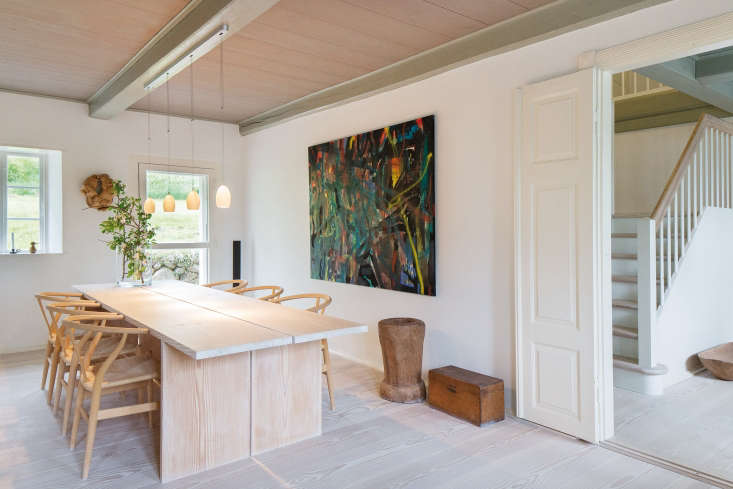 The custom dining table is made from Dinesen Douglas planks. Overhead illumination is provided by Tobias Grau Oh China Lights; the oil painting is by Jens Birkemose.