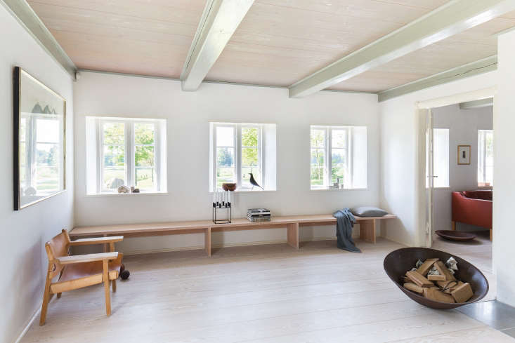 A custom Douglas fir bench. Overby updated the windows and floors of the building to simplify the exterior and modernize the interior. The ceiling beams are original to the house, painted pale green.