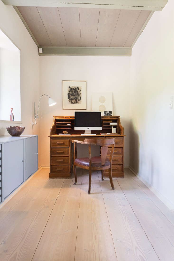 A small office space off one of the bedrooms has a vintage secretary desk, a vintage armchair, and a Bestlite BL 6 Wall Light.