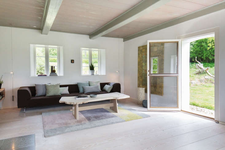 A living space on the main floor is decorated with modern furniture and textiles. The new door to the outside is double-paned glass reinforced with metal.