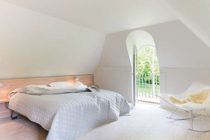 The second bedroom features a custom headboard and aThomas Pedersen Stingray Rocker.