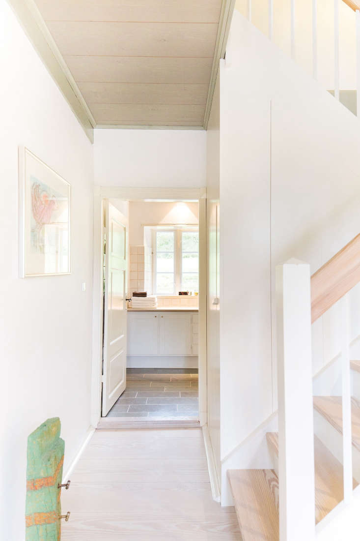 The downstairs bathroom door is painted in tonal off-white with a high-gloss finish.