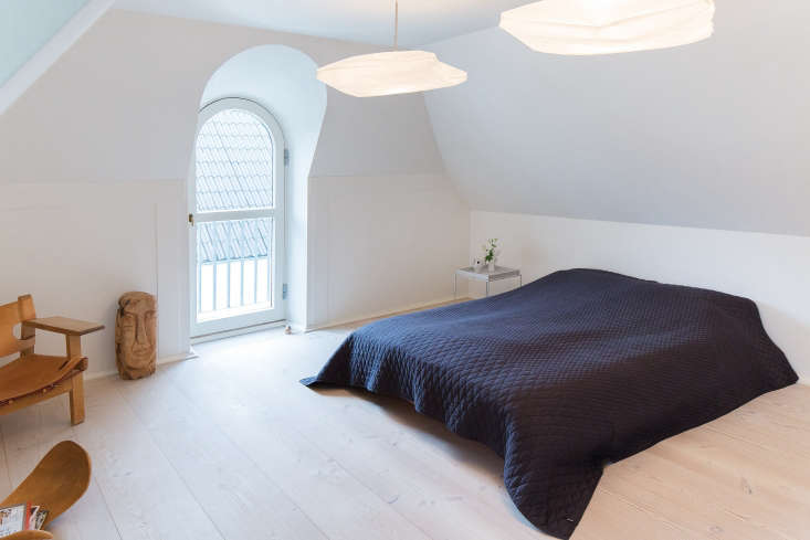 One of the two alcove bedrooms features a black quilt and two paper pendant lights (for something similar you can source Ikea's Varmluft Shade on Amazon).