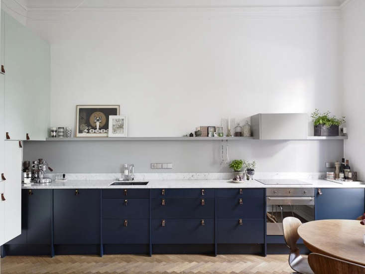 A kitchen in Sweden with dark blue painted cabinets and leather cabinet pulls featured on Swedish real estate site Entrance.