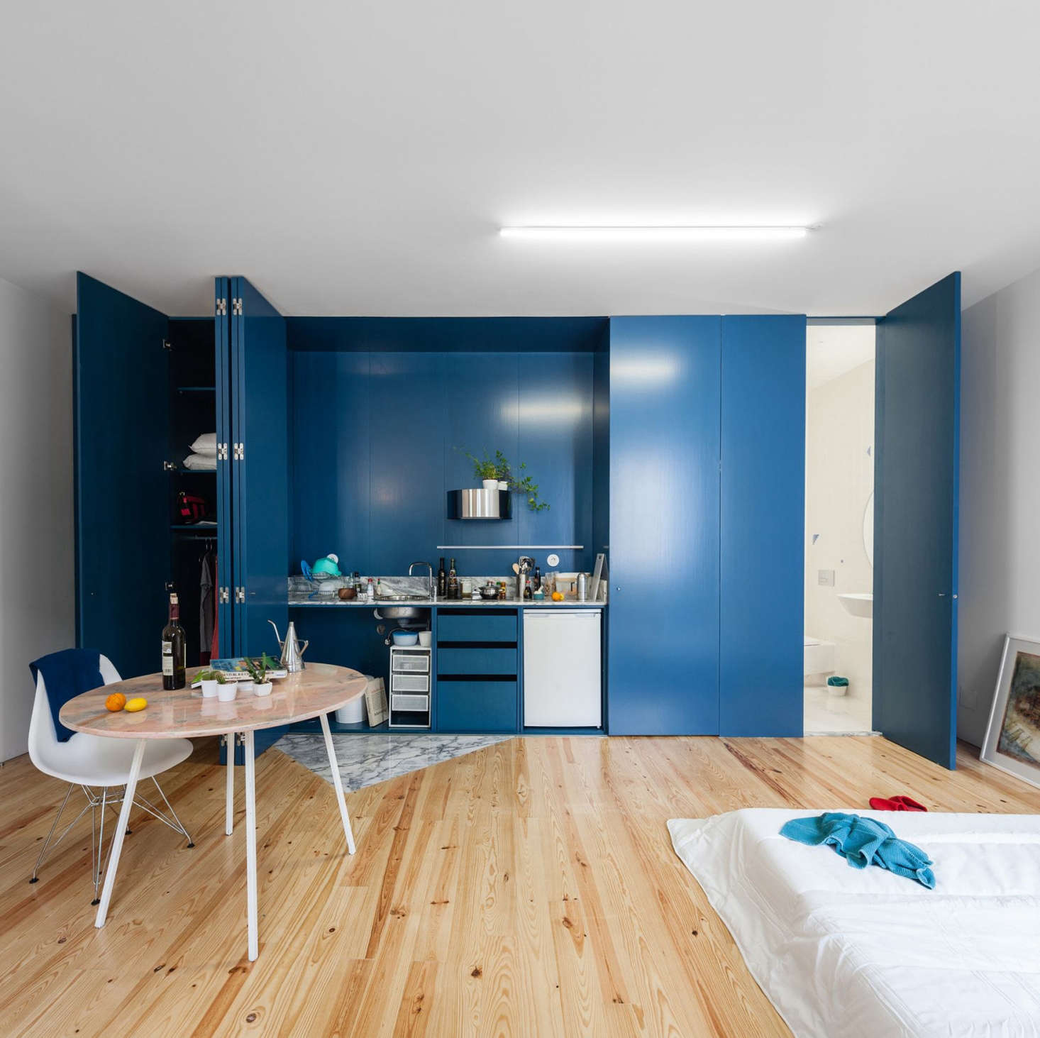 In a house in Porto transformed into studio apartments by Portuguese firmFala Atelier, plywood cabinets conceal everything, including the compact kitchen.