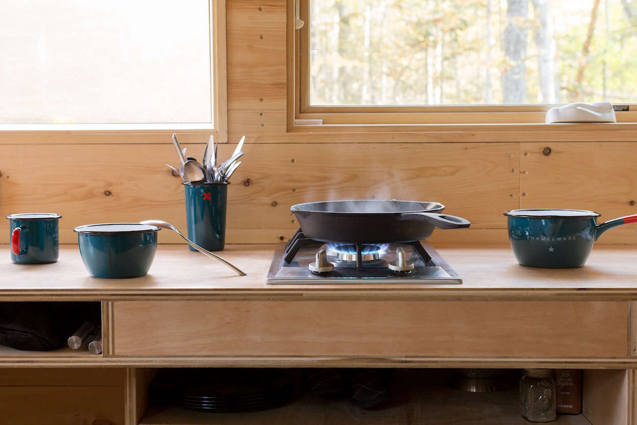 Steal This Look A Stylish Camp Kitchen in a Plywood Summer Cabin A small cooktop accompanied by enamelware dishes and a classic cast iron skillet.Photograph fromGetaway: Instant Camping for the Millennial Set.