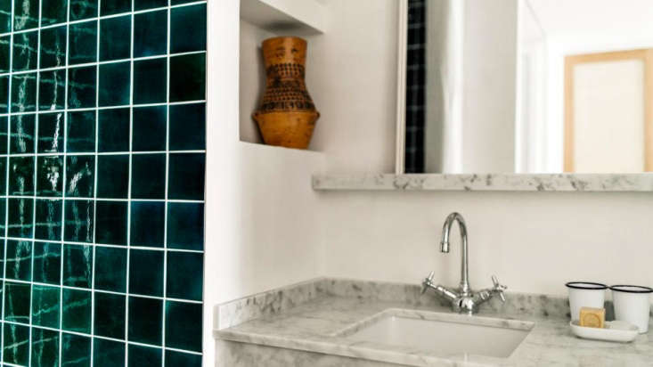 In a guest bath: deep teal tiles and enamelware cups.