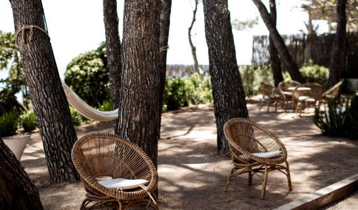 Woven garden chairs and canvas hammocks, for lounging.