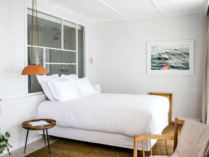 The rooms are whitewashed and simple, with highpaneled ceilings. The architects, a husband-and-wife team, widened windows and added concrete floors to create openness and a vintage feel. Much of the furniture is custom-made by local carpenters, or sourced by Paris-based antiques vendor Alexandre Guillemain.