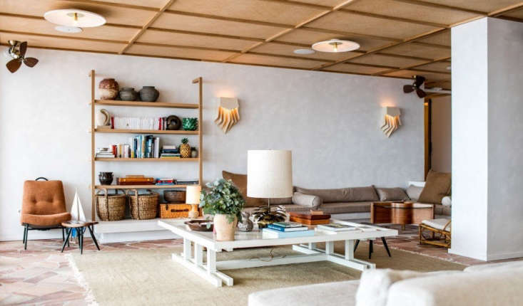 Inside, a lounge with sconces by Guy Bareffand midcentury finds sourced by antique dealers Benjamin Desprez and Hélène Breheret.