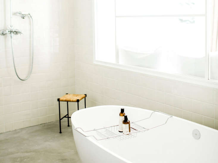 The bath in a Sea View Junior Suite has concrete floors and an exposed, no-frills shower.
