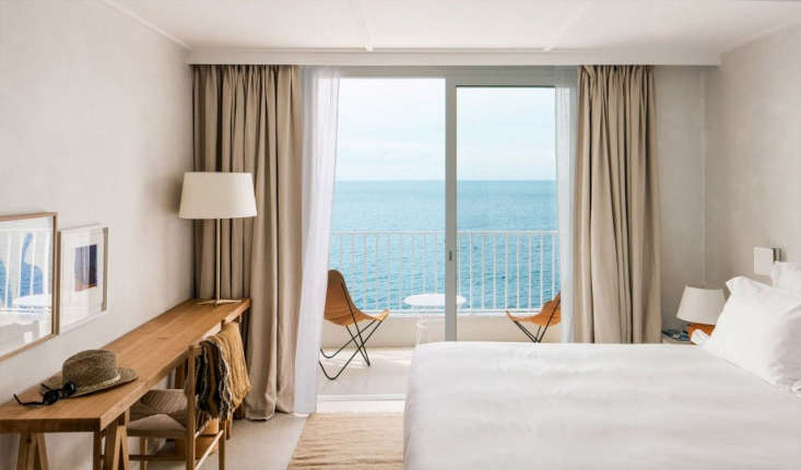 The guest rooms feature white linens, natural-fiber rugs, and balconies with bright canvas chairs. Shown here:a Sea View Superior Room.