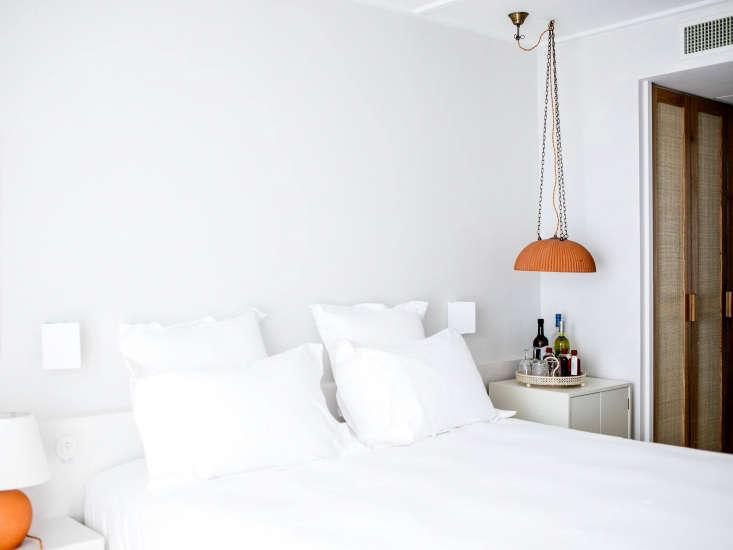 Marigold-hued pendant lights hang by the bedside (and above a deconstructed minibar).