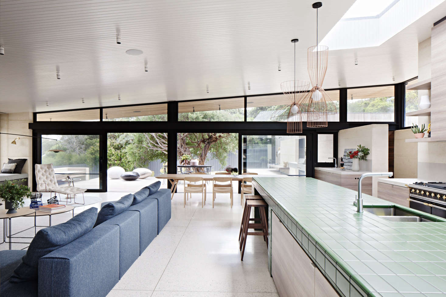 Designed as a gathering place for a multigenerational family and their many guests, the house revolves around a central living/dining/cooking area with a clean-lined, organic-modern look.