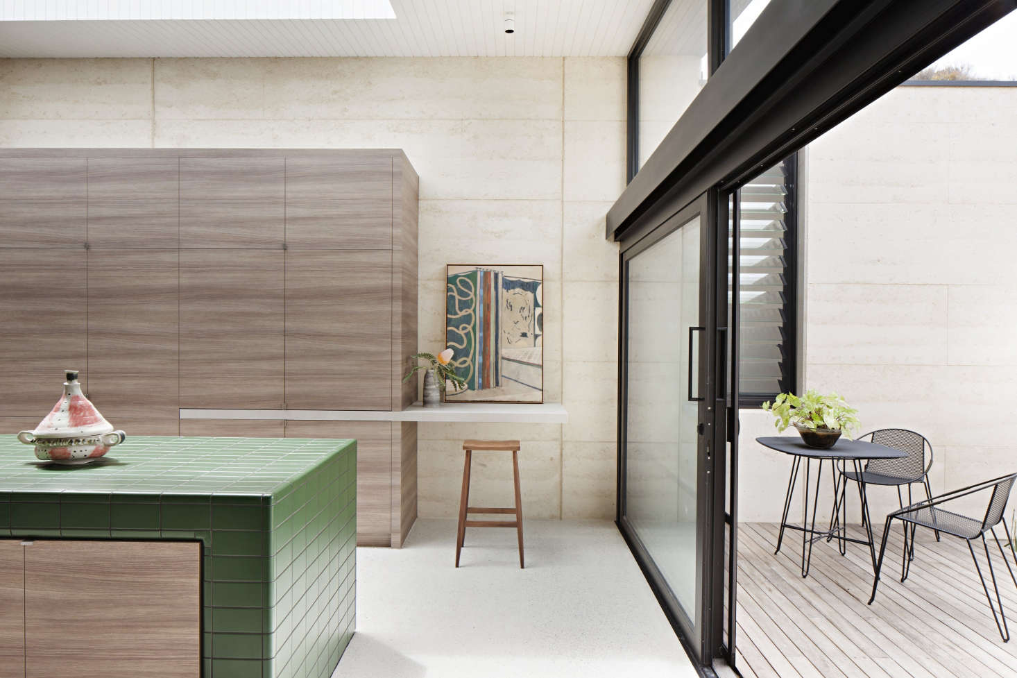 The kitchen opens to a small terrace. The large oak cabinet conceals, among other things, the refrigerator and an appliance cupboard.