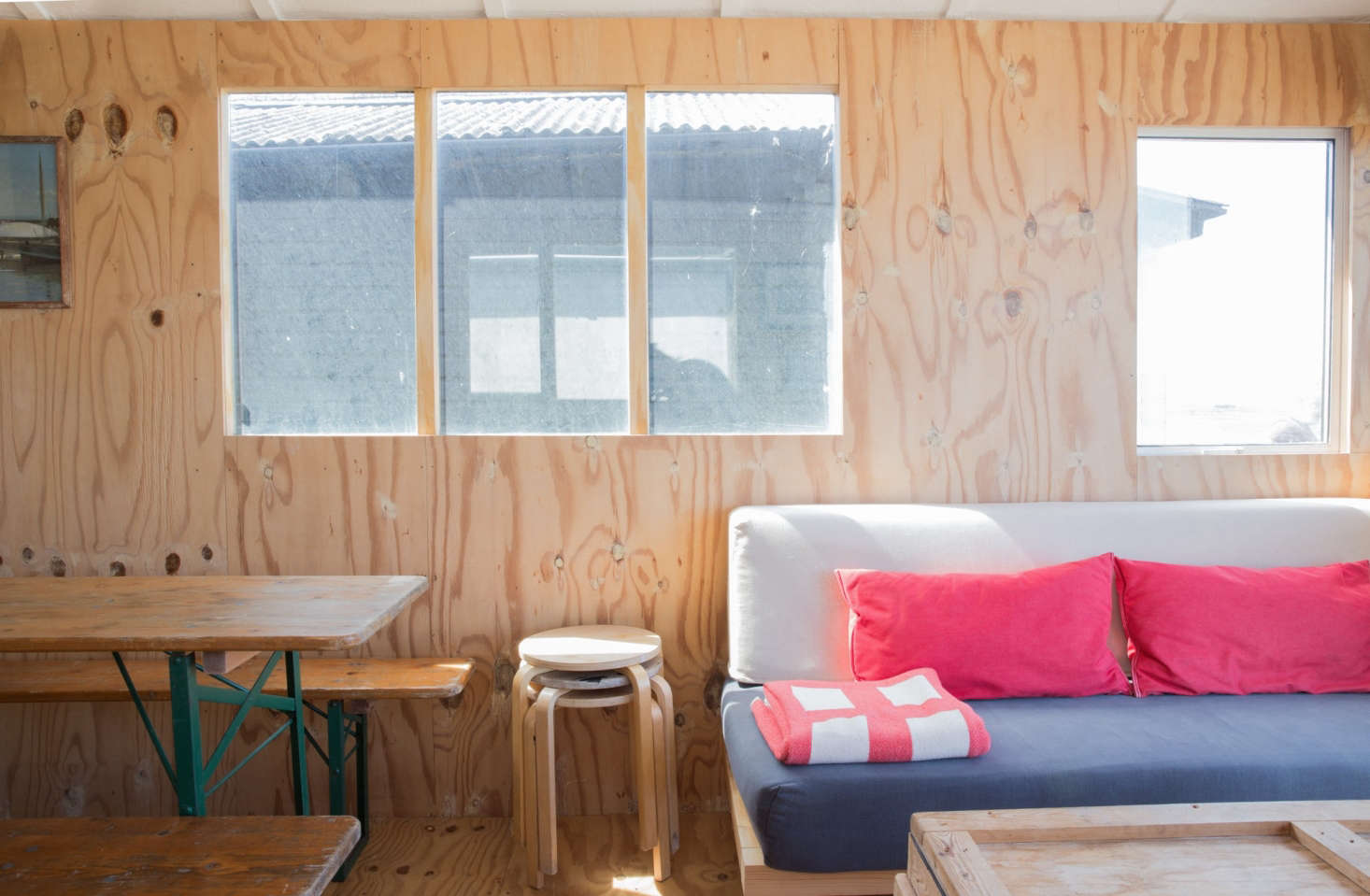The sofa, which serves as an extra bed, is a homemade wooden platform—&#8