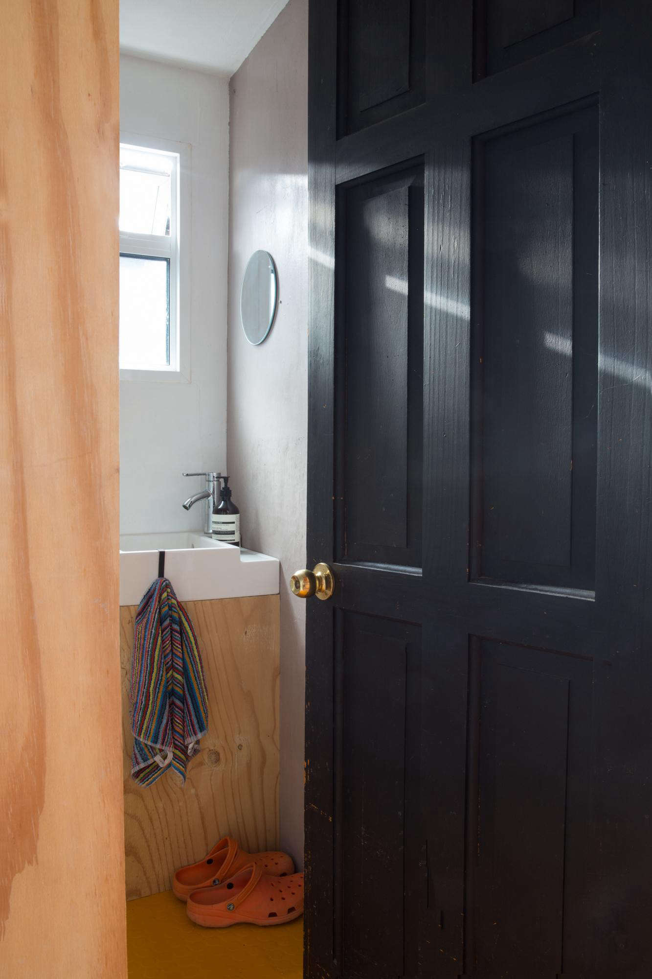 The tiny plywood bathroom has just enough room for the door to open. &#8